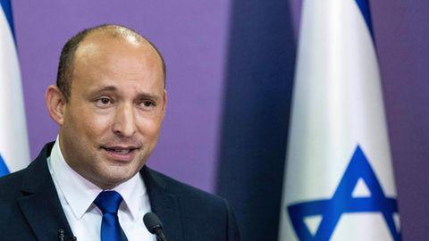 Mit Israel-Flaggen im Hintergrund steht ein weißer Mann mit Halbglatze und rasierten Haaren im Anzug an einem Rednerpult