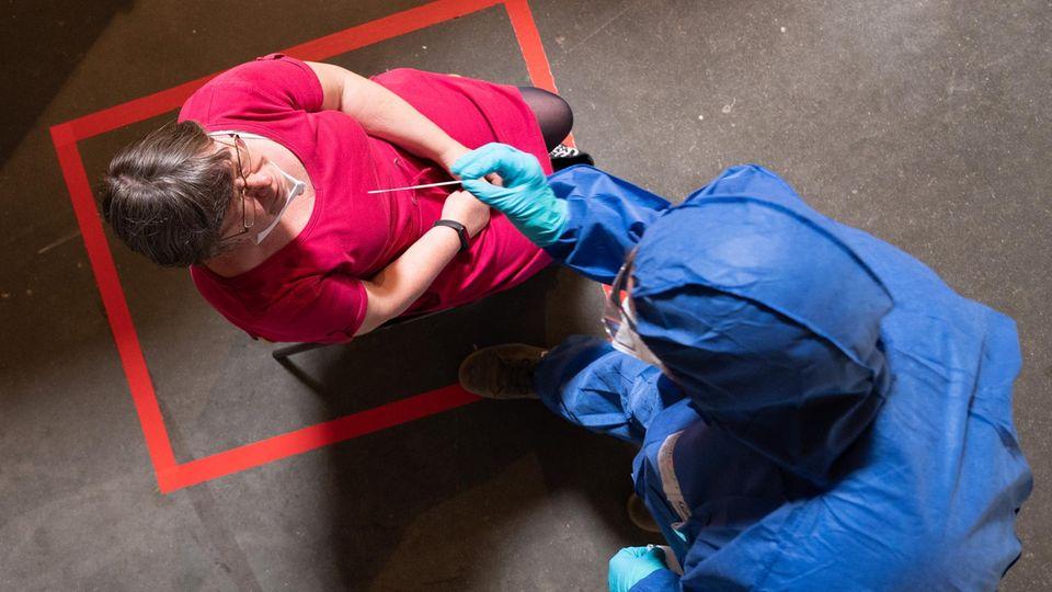 Eine Frau sitzt in einem Testzentrum und wird von einemMitarbeiter Deutsches Rotes Kreuz auf das Coronavirus getestet