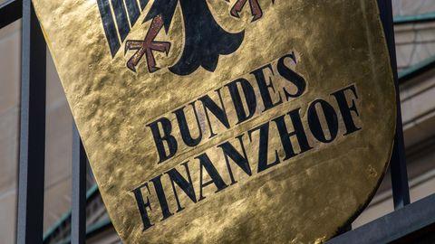 """Ein Wappenschild zeigt den schwarzen Schriftzug """"Bundesfinanzhof"""" unter dem Bundesadler auf goldenem Grund"""