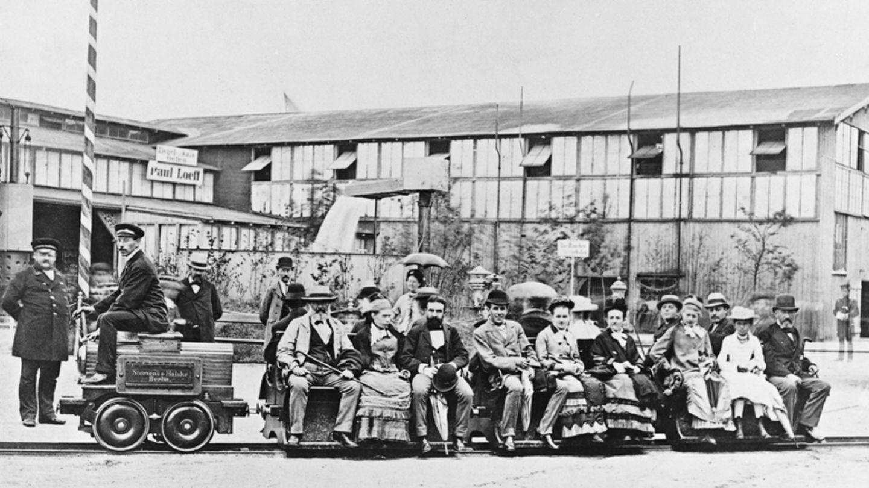 """31. Mai 1879: Werner Siemens führt erste praxistaugliche Elektrolokvor  Groß war die Maschine nicht, und ihr Weg war kurz, dennoch hat die Fahrt der kleinen Elektrolok auf einem nur 300 Meter langen Rundkurs auf der Berliner Gewerbeausstellung am 31. Mai 1879 eine neue Ära eingeläutet. Die bei Siemens und Halske entwickelte Lokomotive bewies, dass sie eine größere Anzahl von Personen transportieren konnte und erwies sich damit als erstes Exemplar als praxistauglich. Wenn man so will ein früher Meilenstein derE-Mobilität. Werner Siemens, später """"von Siemens"""", präsentierte seine Entwicklung mit Stolz. Der Industrielle ist bekannt als Begründer der modernen Elektrotechnik und Entdecker des elektrodynamischen Prinzips, der Grundlage für elektrische Generatoren."""