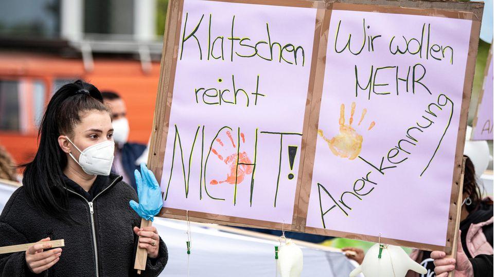 Eine Pflegekraft hält ein Protestschild in die Höhe