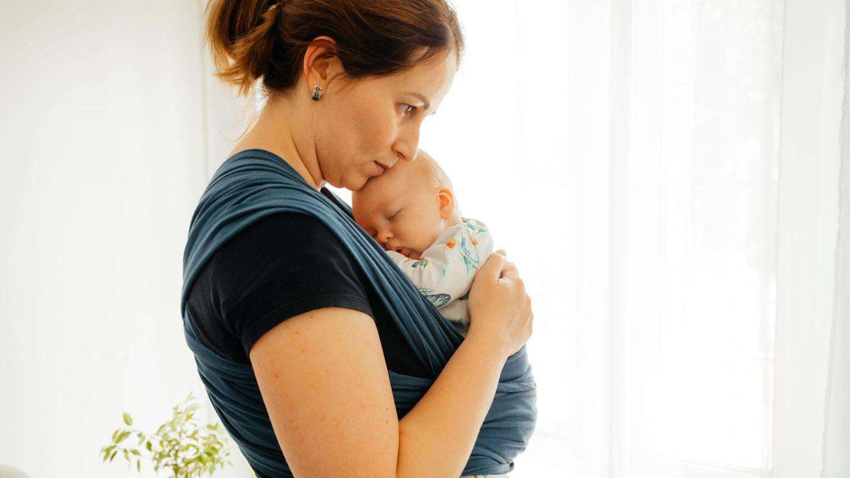 Eine junge Mutter trägt ihr Baby in einem Tragetuch vor der Brust