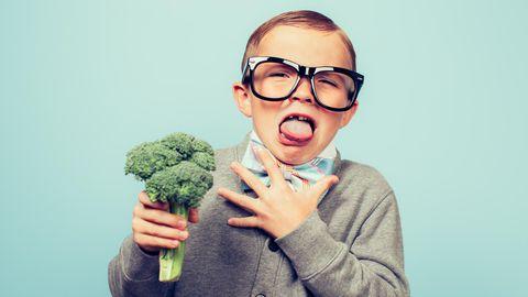 Kleiner Junge mit Brille ekelt sich vor einem Brokkoli, den er in der Hand hält