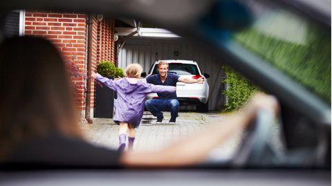 Kind läuft dem Vater in die Arme und die Mutter beobachtet das aus dem Auto heraus