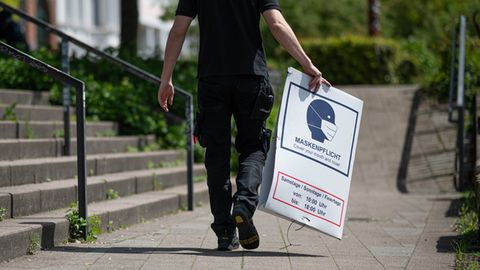 Mann trägt Maskenpflicht-Schild