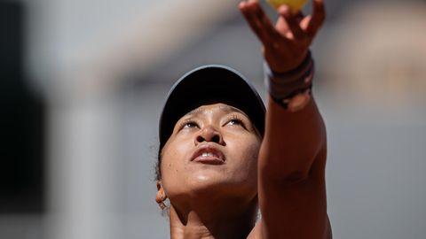 Eine asiatisch aussehende Frau schaut bei Sonnenschein hoch zum Tennisball, den ihre linke Hand gerade hochwirft