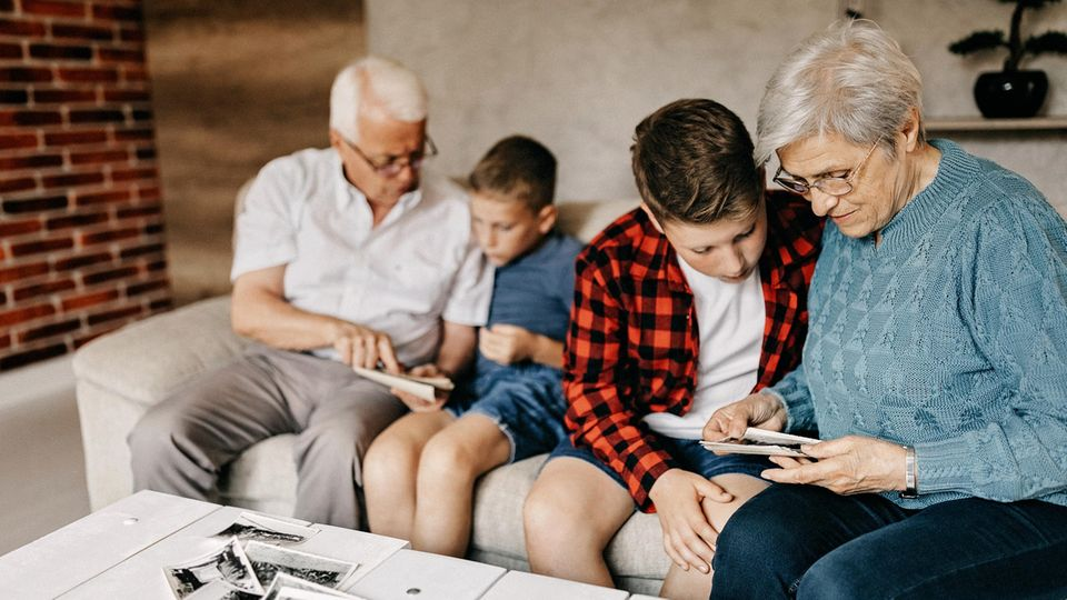 Ahnenforschung: Großeltern gucken sich gemeinsam mit ihren Enkeln alte Bilder an