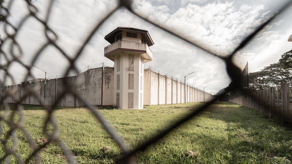 Blick durch Maschendrahtzaun auf Gefängnismauer und Wachturm