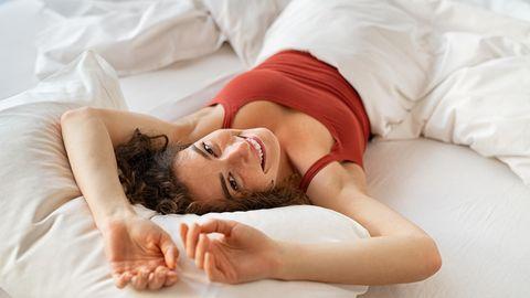 Junge Frau liegt entspannt im Bett