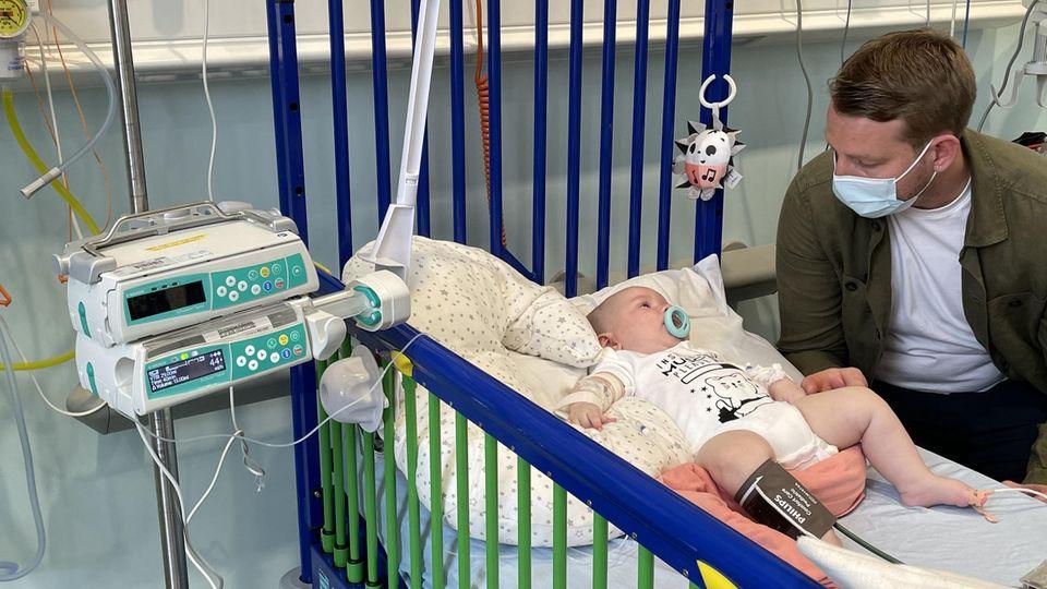 Arthur liegt in einem Krankenhausbett, sein Vater sitzt daneben
