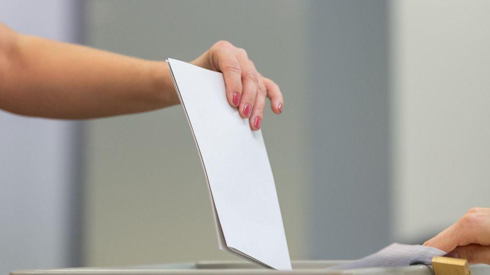 Eine Frau wirft ihren Stimmzettel in eine Wahlurne