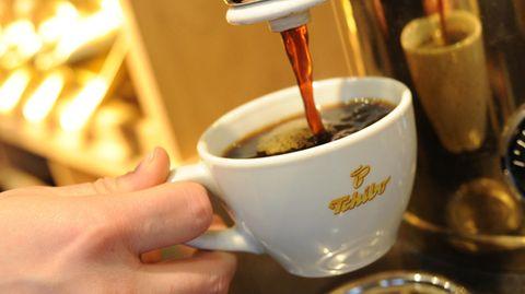 Ein Tchibo-Mitarbeiter füllt eine Kaffeetasse