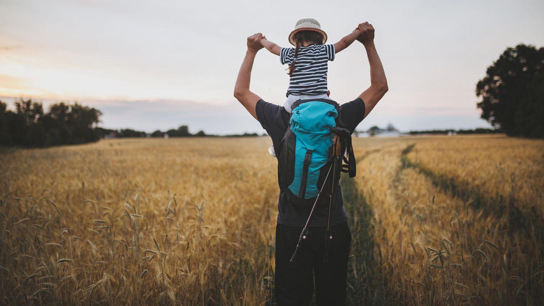 Vater trägt junge Tochter auf den Schultern durch ein Feld
