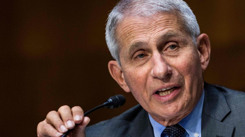 Ein weißhaariger weißer Mann im Anzug biegt mit der rechten Hand ein kleines schwarzes Mikro beim Sprechen an sein Gesicht