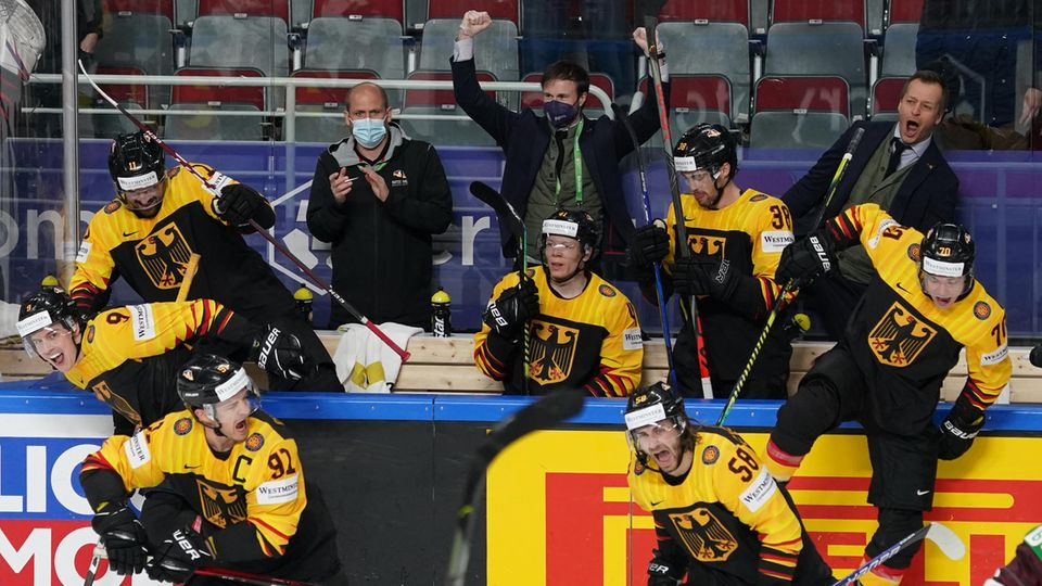 Deutsche Eishockeyspieler überspringen jubelnd die Bande