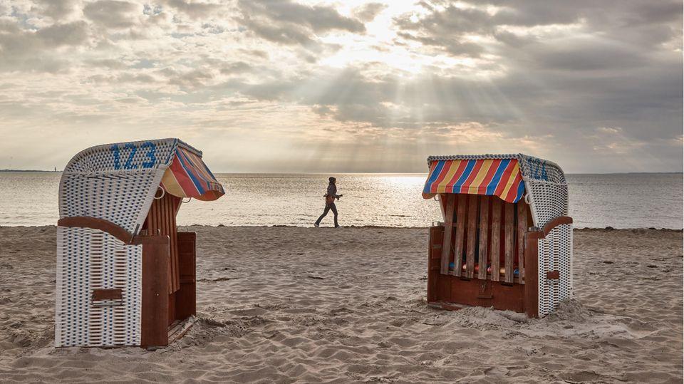 Eine Frau joggt am Strand entlang. Im Vordergrund sind zwei Strandkörbe zu sehen.