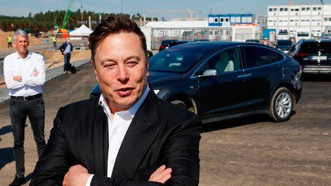 Ein weißer Mann in Anzug und weißem Hemd steht mit verschränkten Armen vor einem dunkelgrauen Sportwagen auf einer Großbaustelle