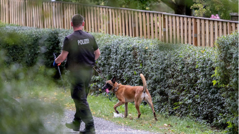Ein Polizeibeamter mit einem Hund durchsucht eine Kleingarten-Parzelle