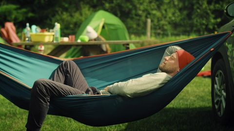 Outdoor Hängematte: Junger Mann schläft auf einem Zeltplatz in der Hängematte