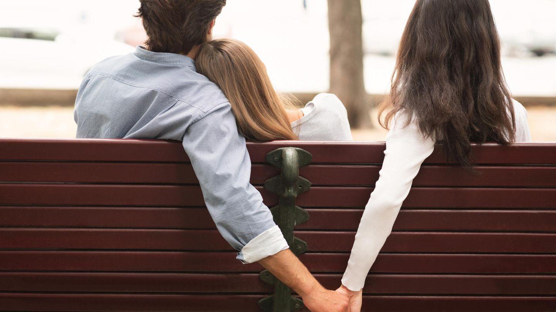Pärchen sitzt auf einer Bank. Der Mann hält hinter der Bank die Hand einer zweiten Frau.