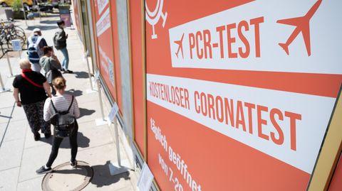 Sachsen, Dresden: Passanten warten vor einem Corona-Testzentrum