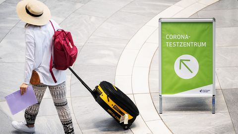 Frau mit Koffer geht zu einem Corona-Testzentrum