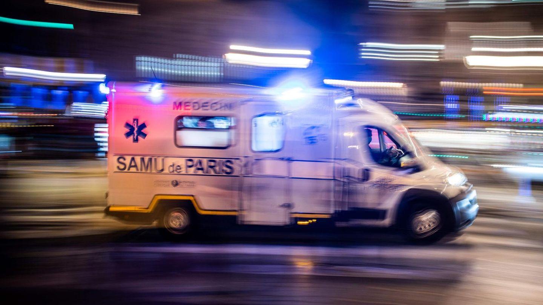 """Ein weißer Transporter mit Blaulicht und """"Samu Paris""""-Schriftzug fährt durch eine nächtliche Stadt"""