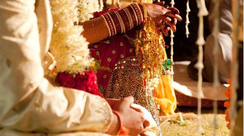 Die Hände eines indischen Paars in Hochzeitskleidung