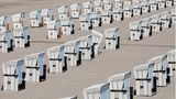 Warnemünde, Deutschland. Aufgereiht wie auf Perlenschnüre stehen Strandkörbe am Ostseestrand. Von diesem Freitag an ist Mecklenburg-Vorpommern nach der langen Corona-Pause wieder für Urlauber aus ganz Deutschland geöffnet. Eine Woche später sollen dann auch Tagesausflügler wieder willkommen sein. Dann dürfte es mit der beschaulichen Ruhe, die die vereinzelten Badegäste derzeit vielleicht noch genießen, vorbei sein. Die Freude, dass wieder Strandleben einzieht, wird aber größer sein.