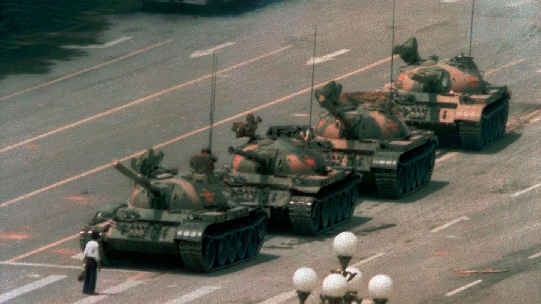 """Ein Bild, das um die Welt ging. Alleine stellt sich ein Mann unweit des Platzes am Tor des Himmlischen Friedens in Peking, dem Tian'anmen, einer Reihe Panzer entgegen. Es wurde zum Sinnbild für die gewaltfreie, ursprünglich studentische Demokratiebewegung, die durch Reformbestrebungen in der Sowjetunion, Polen und Ungarn inspiriert worden war und von Chinas Militär blutig niedergeschlagen wurde. Laut Quellen aus dem Roten Kreuz Chinas starben in den Tagen nach dem 4. Juni in ganz Peking 2600 Aufständische und Militärs, Tausende wurden verletzt. Obwohl auf dem Platz selbst niemand starb, ging das Blutbad als Tian'anmen-Massaker in die Geschichte ein. Auslöser war, dass China wegen der Besetzung des Platzes durch die Demokratiebewegung den sowjetischen Präsidenten Michail Gorbatschow dort nicht empfangen konnte – weshalb sich die Demokratiebewegung vor der Weltpresse nicht mehr klein reden ließ. Mit dem Massaker endeten vorerst politische Reformen, die seit 1986 von Parteichef Deng Xiaoping eingeleitet worden waren. Auch heute unterdrückt China jedes Gedenken an den, so offiziell """"Zwischenfall vom 4. Juni""""."""