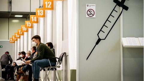 Menschen warten im Corona-Impfzentrum