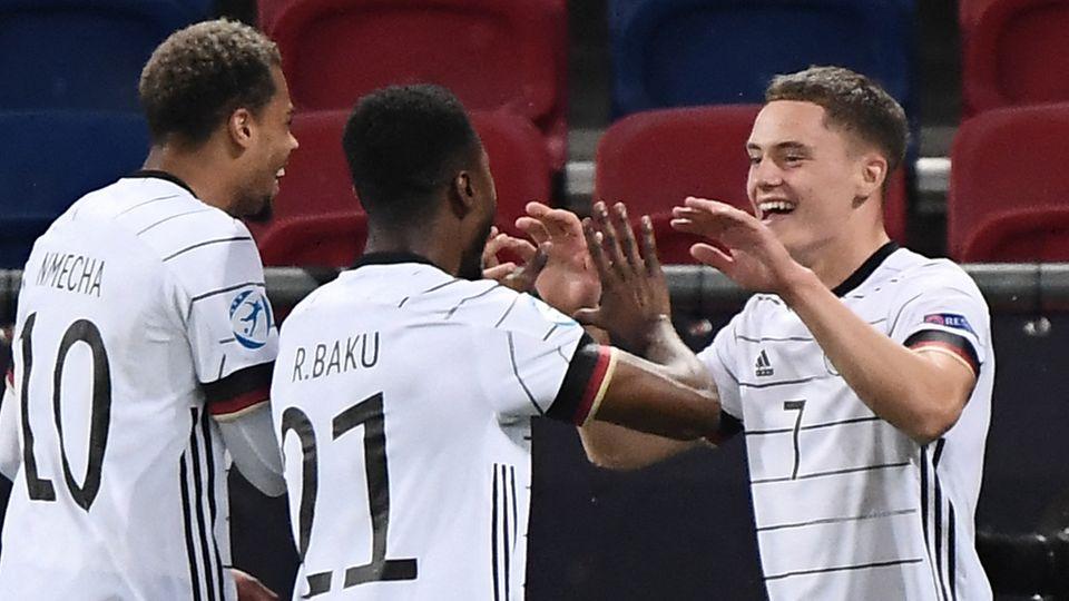 Lukas Nmecha und Ridle Baku gratulieren Florian Wirtz nach seinem zweiten Treffer gegen Holland