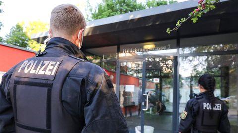 Ein blonder Polizist und eine dunkelhaarige Polizistin sind von hinten zu sehen, wie sie auf einen gläsernen Eingang zugehen