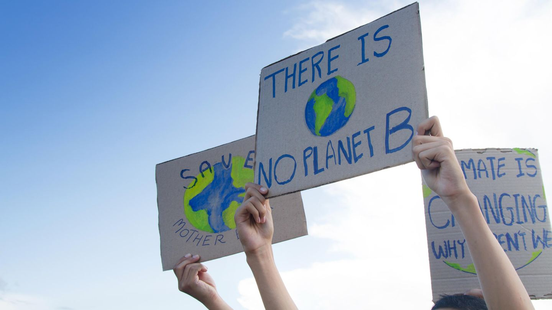 """Hände halten Transparente mit der Aufschrift """"There is no planet B"""" hoch"""
