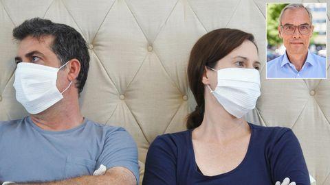 Ein Mann und eine Frau lehnen sich mit verschränkten Armen an das Kopfteil eines Bettes und schauen voneinander weg