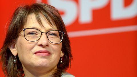 Eine weiße Frau mit schulterlangen braunen Haaren und braunem Brillengestell unter einem weißen SPD-Schriftzug auf rotem Grund