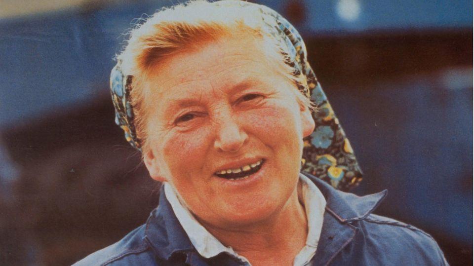 """Eine Bäuerin in blauer Arbeitskluft und Kopftuch: Mit Kampagnen wie diesen setzte das DDR-Regime arbeitende Frauen in Szene.Nicht zu arbeiten galt als """"asozial"""" – Arbeitslosigkeithing ein soziales Stigma an."""
