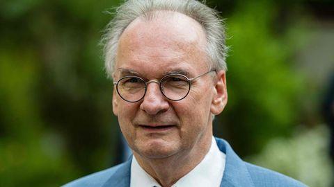 Ein Mann mit Brille und schütter werdendem grauen Haar trägt ein hellblaues Jackett mit farblich passender Krawatte