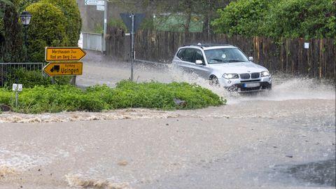 Ein Fahrzeug fährt durch eine Straße, die nach einem starken Gewitter überflutet ist