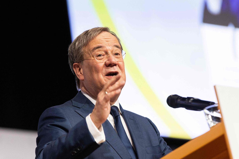 Ein weißer Mann in blauem Anzug steht vor einem Mikrofon und gestikuliert mit seiner rechten Hand auf Höhe seines Kinns