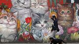 Buenos Aires, Argentinien. Eine Frau führt ihren Hund im Viertel Villa Crespo der argentinischen Hauptstadt aus – vor einem Wandgemälde mit Katzen.