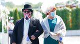 Epsom, Großbritannien. Diese beiden Besucher des Cazoo Derby Festival verzichten auch in Corona-Zeiten nicht auf ihren Auftritt in feiner Garderobe – mit auffallender Kopfbedeckung undMund-Nasen-Schutz.