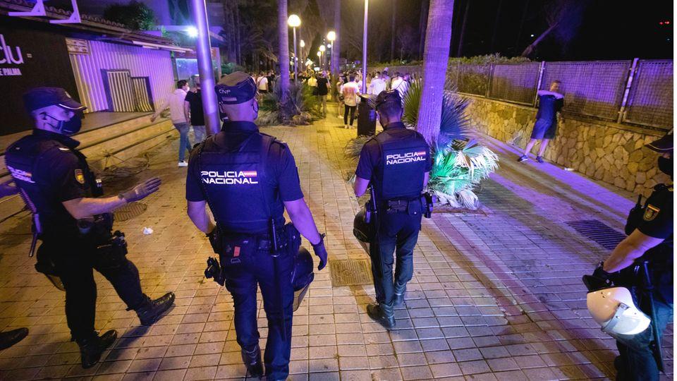 Nach der Sperrstunde der Bars feiern die Menschen am Strand von El Arenal. Die Polizei schickt das Partyvolk immer wieder weg.