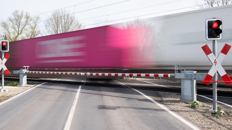 Hinter zwei geschlossenen Schranken quert ein Güterzug mit Containern eine Straße. Die Waggons sind wegen des Tempos unscharf