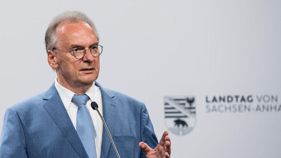 """Vor einer weißen Wand mit schwarzem """"Landtag von Sachsen-Anhalt"""" steht ein grauhaariger Mann in blauem Anzug und spricht"""