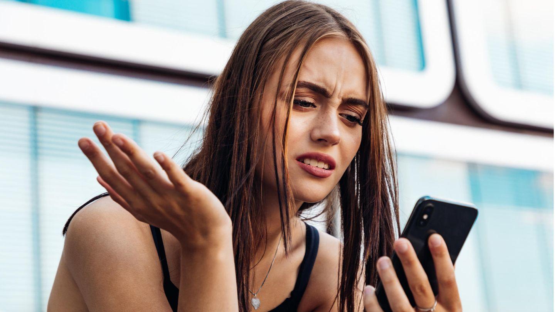 Frau schaut verständnislos aufs Handy