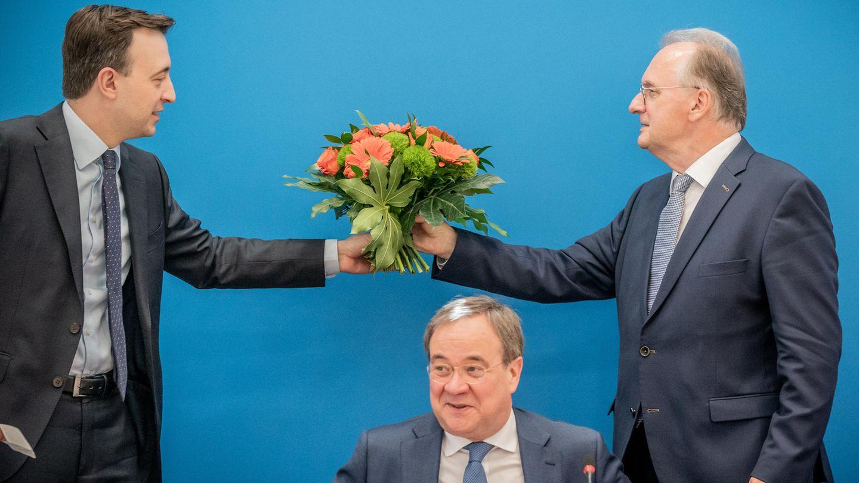 Reiner Haseloff (CDU, r) übergibt den Blumenstrauß, den er von Armin Laschet (M) erhalten hat erhalten hat