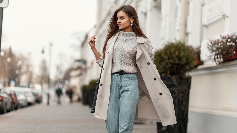 Frau auf der Straße in Mom Jeans und Trenchcoat