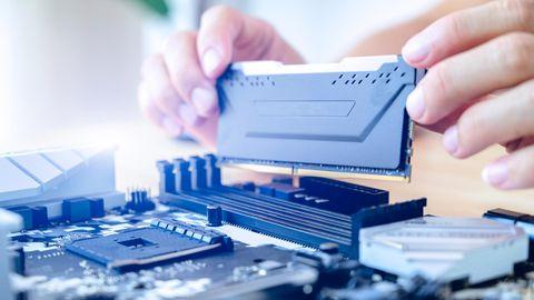 Aufrüstkit: Eine Person steckt einen RAM-Riegel in den entsprechenden Slot.