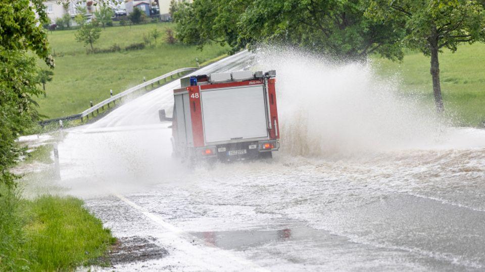 Ein Fahrzeug der Feuerwehr fährt im Ortsteil Brombach auf einer Straße, die nach einem starken Gewitter überflutet ist.